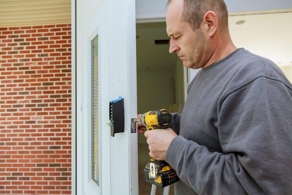 Installation d'une porte intérieure verrouillée mains de menuisier installer une serrure Installation de la serrure de la porte.